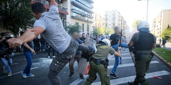 левый активист ногой бьет полицейского по спине